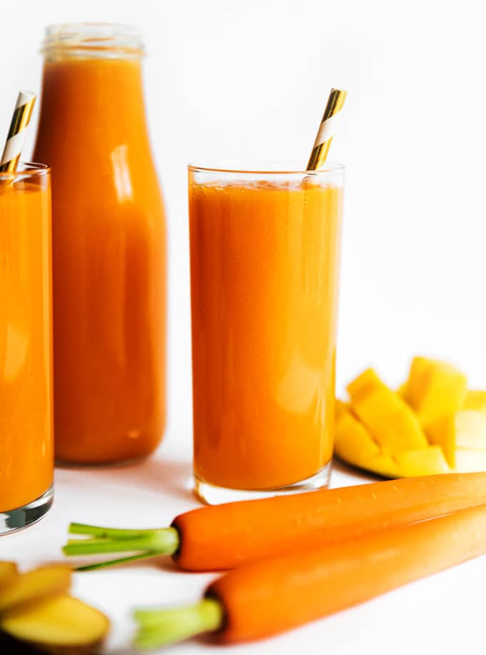 Tropical carrot juice recipe in three glasses on a white background