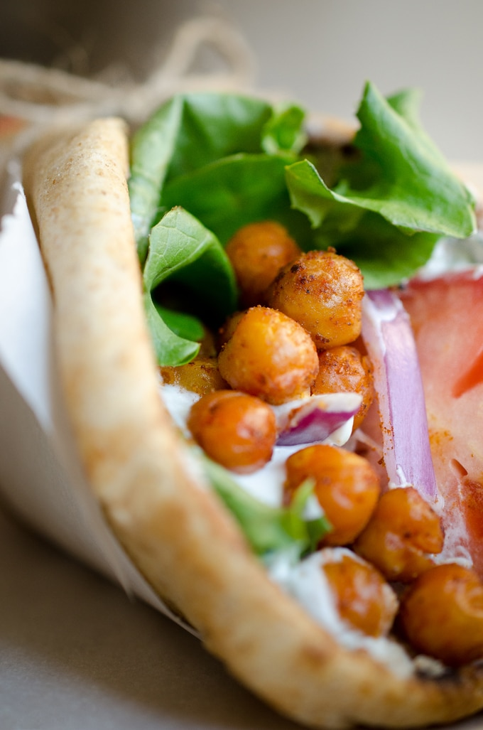 Close up photo of roasted chickpea gyros with tomato and lettuce in a pita wrap