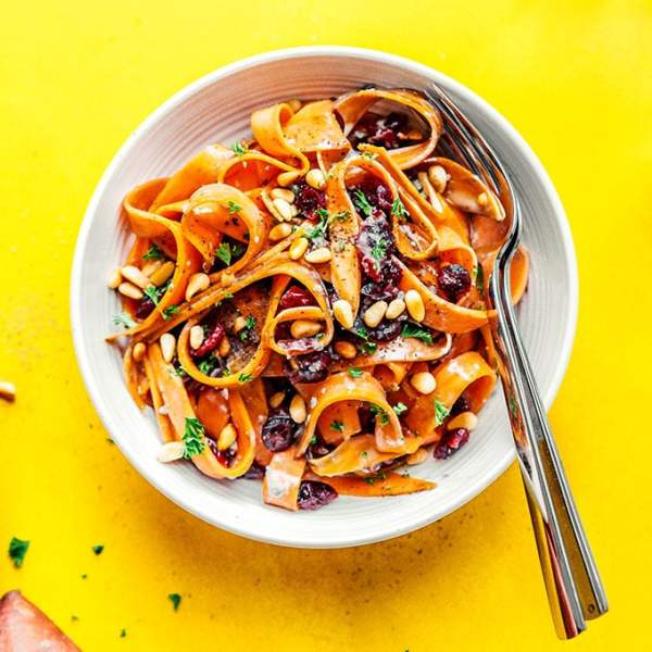 Sweet potato fettuccine noodles in a bowl on a yellow background