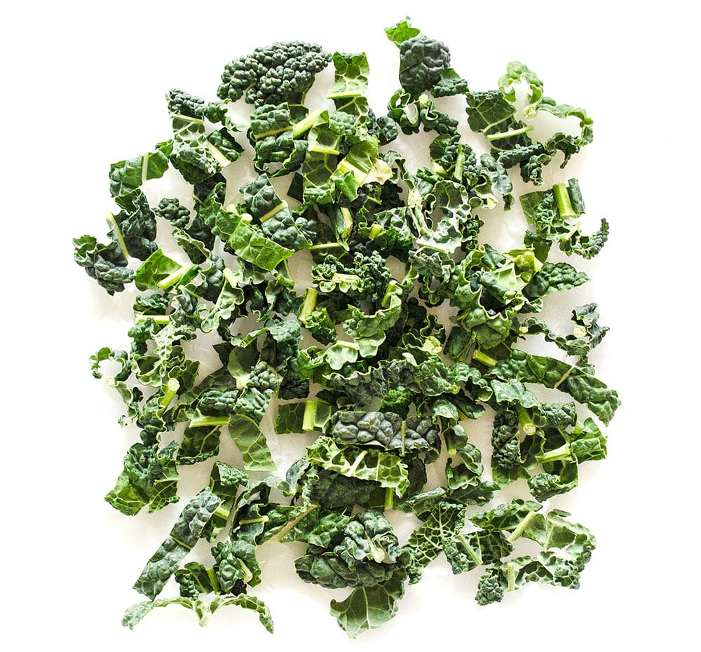 Photo of chipped kale on white background