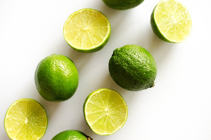 Lime fruits cut in half on a white background