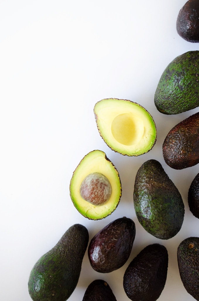 Photo of avocado cut in half on white background