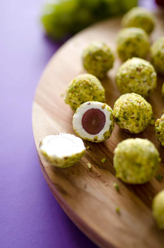 Grape goat cheese bite cut in half - These goat cheese covered grapes rolled in pistachios are crunchy on the outside, creamy on the inside, and bursting with juicy flavor!