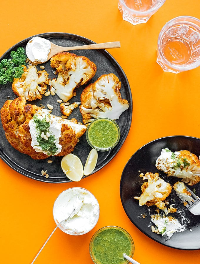Marinated cauliflower on a plate with herb sauce and whipped feta cheese