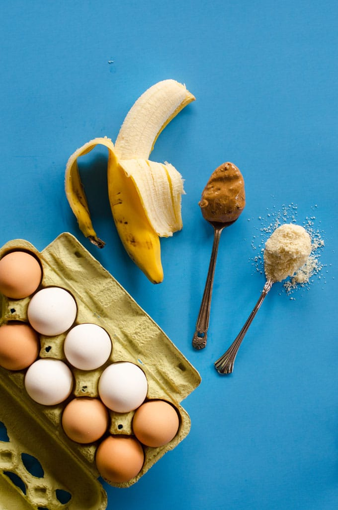 Ingredients to make paleo pancakes on a blue background