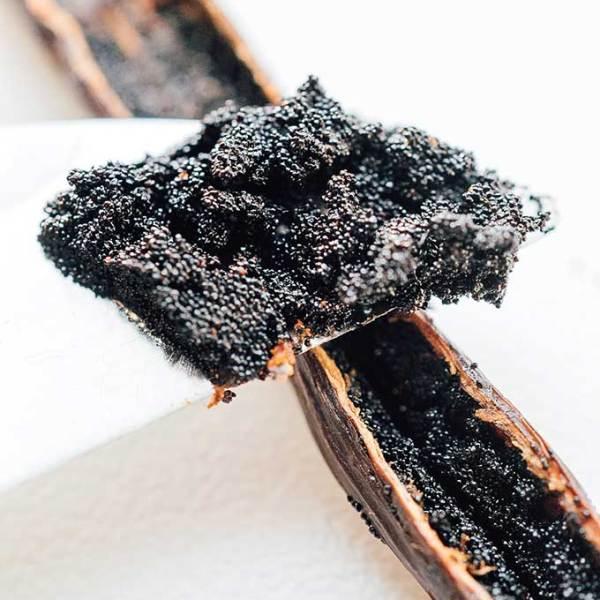Closeup photo of vanilla bean seeds on a knife from a vanilla pod