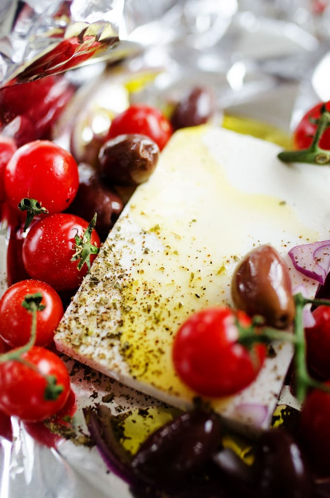 Baked feta with tomatoes, olives, and red onion in a foil packet