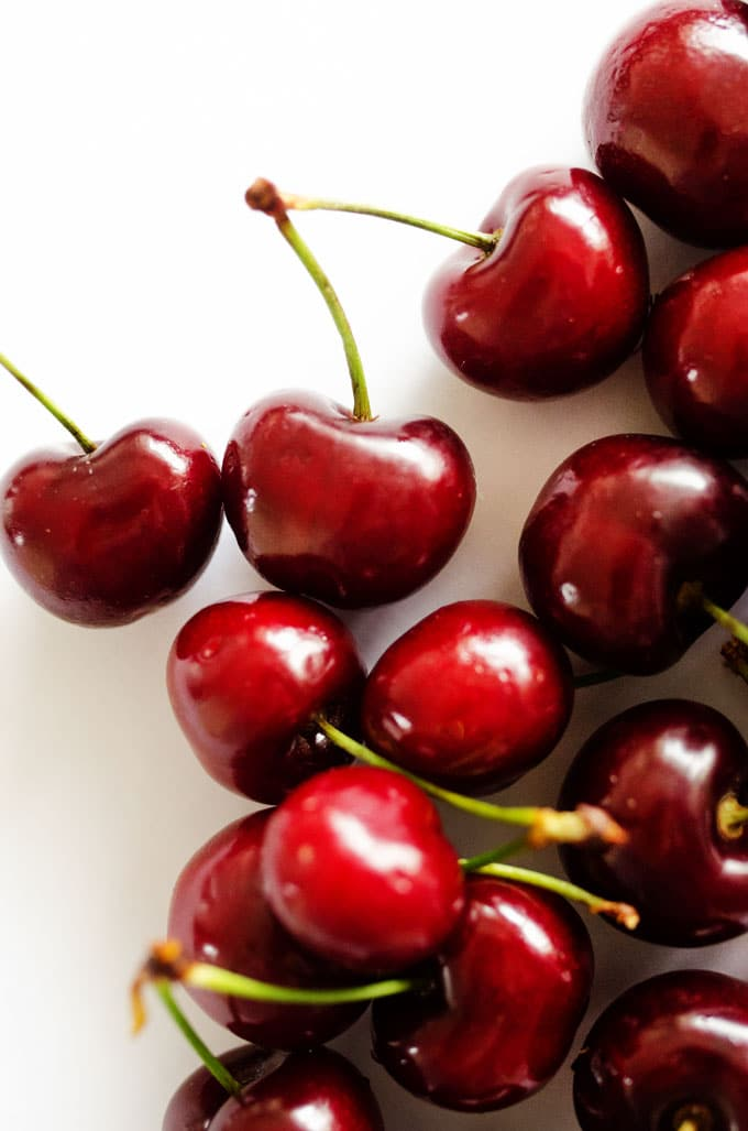 Close up photo of cherries on white background