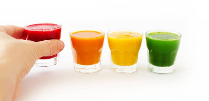 Rainbow smoothie shots on a white background