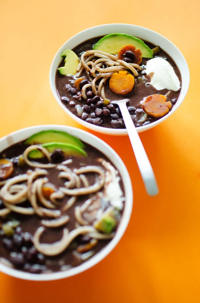 Halloween soup with black beans, udon noodles, and Halloween-shaped vegetables.
