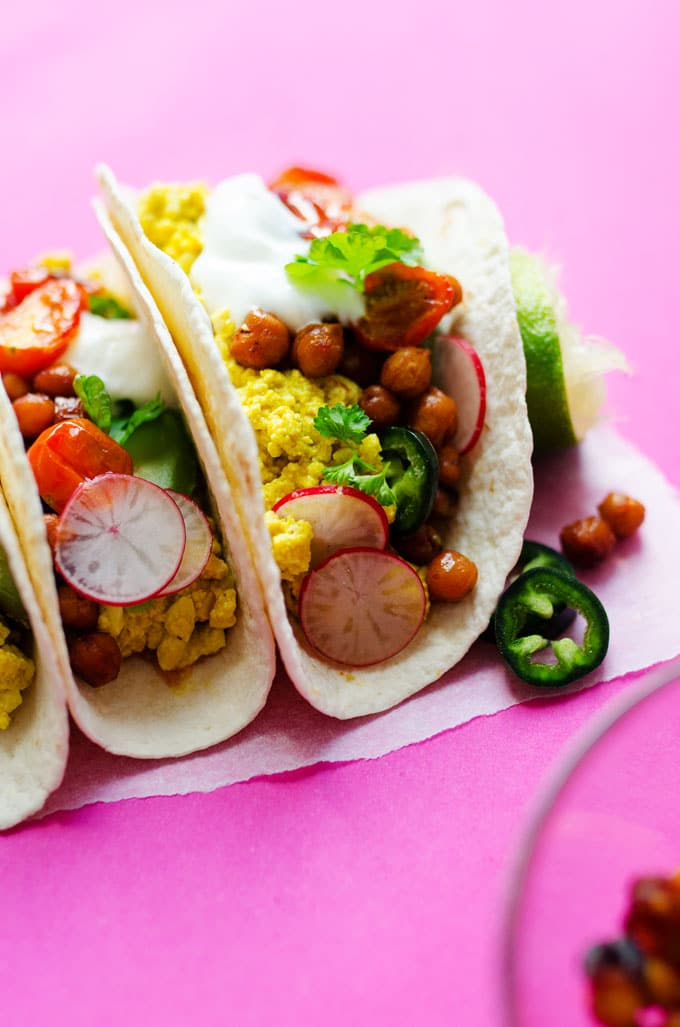 """Vegan tofu scramble tacos on a pink background - These Vegan Breakfast Tacos are stuffed with flavorful tofu scramble, """"bacon-y"""" crispy chickpeas, and smoky roasted tomatoes (all in under 30 minutes!)"""