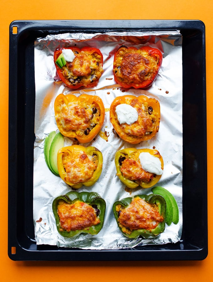 Quinoa stuffed peppers on a baking sheet with melted cheese, sour cream, and avocado - Need a healthy vegetarian dinner outside of your usual routine? These Enchilada Quinoa Stuffed Peppers flavored with a quick homemade enchilada sauce and baked to bubbly, cheesy, perfection.