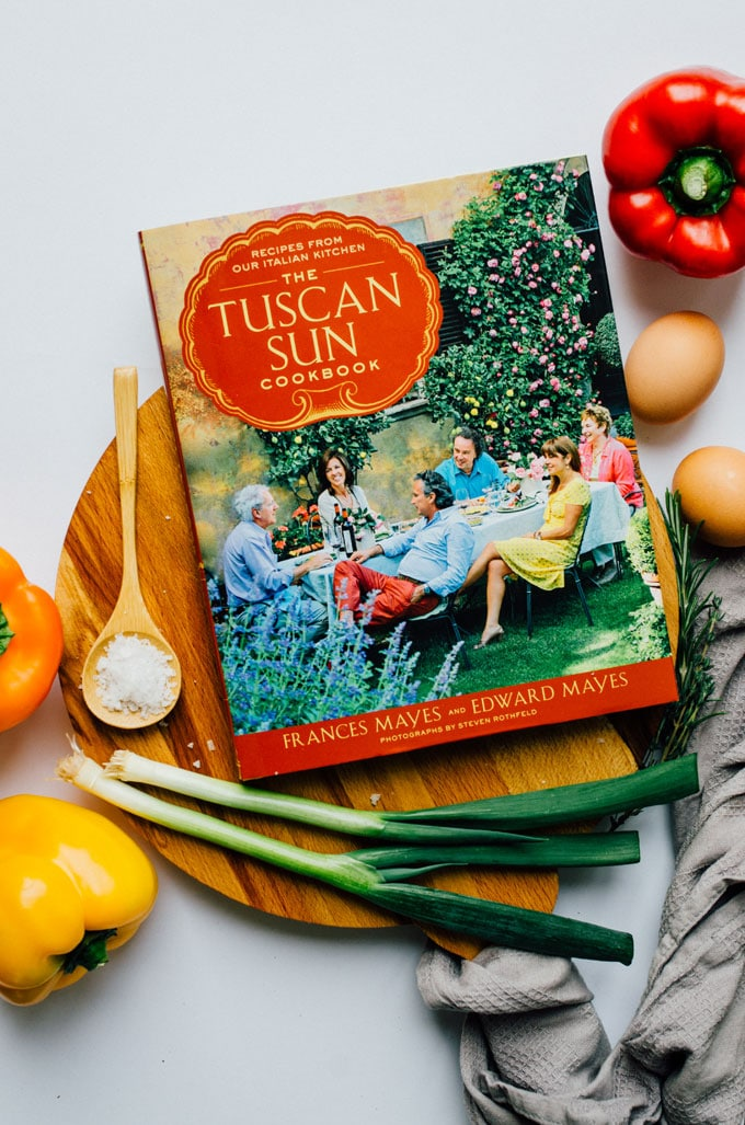 Tuscan Sun Cookbook on a cutting board surrounded by ingredients - These Herby Ricotta Stuffed Peppers taste straight out of Tuscany with fresh herbs, creamy ricotta, and sharp parmesan.