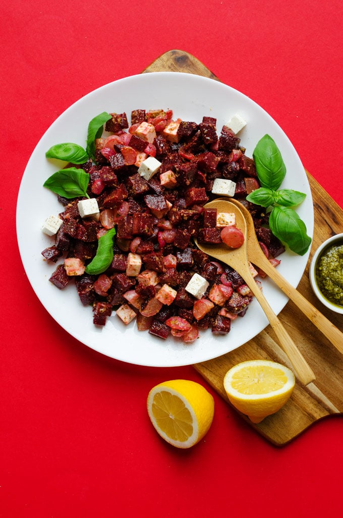 Roasted beet and radish salad with feta cheese on a wooden board on a red background - Here's a way to make your beets NOT taste like dirt! This Roasted Beet an Radish Salad is loaded with fresh pesto, feta cheese, and a hint of lemon, which help to counter that typical beet taste that so many of us can't get over.