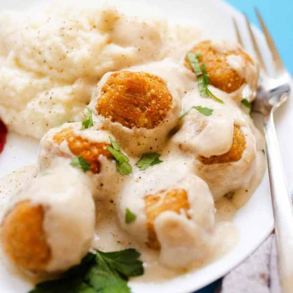 These Swedish Quinoa Meatballs are a healthy combination or quinoa and cauliflower, smothered in simple cream sauce and served atop fluffy mashed cauliflower! No need to go furniture shopping to have a taste of Sweden.