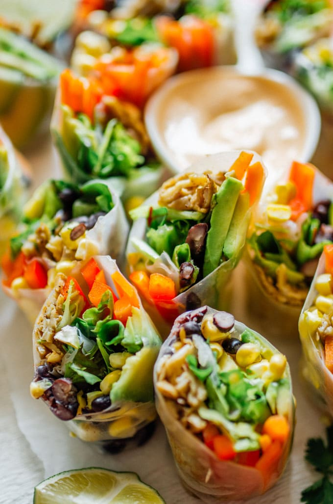 Closeup of spring rolls - These vegetarian Southwest Spring Rolls are packed with fresh vegetables and dipped in a smoky chipotle sauce. You'll forget how healthy they are as you devour the whole pile!