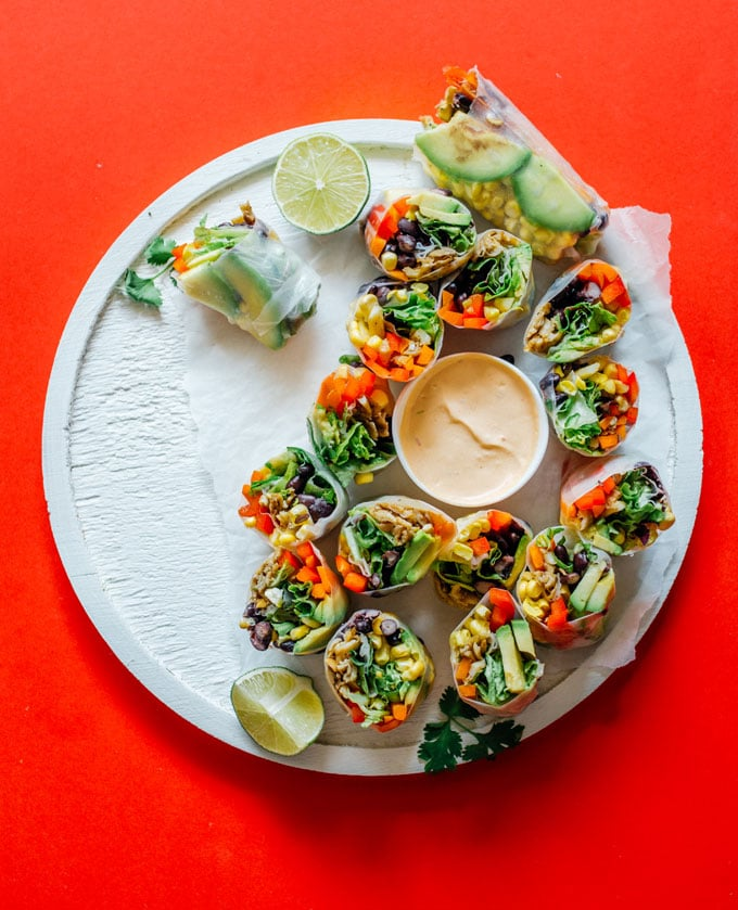 Spring rolls on red background white plate - These vegetarian Southwest Spring Rolls are packed with fresh vegetables and dipped in a smoky chipotle sauce. You'll forget how healthy they are as you devour the whole pile!
