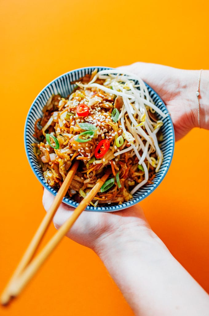 Egg roll bowl on orange background in blue striped bowl - This Vegetarian Egg Roll in a Bowl is the laid back egg roll you didn't know you needed. It has all the tasty fillings found in your favorite egg rolls, subbing out the pork for pulled oyster mushrooms!