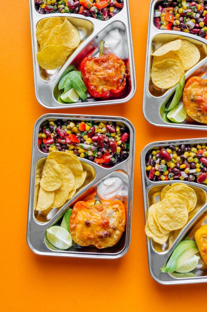 Meal prep containers with bean salad and stuffed peppers on an orange background