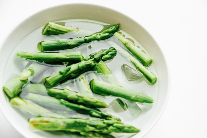 Boiled asparagus recipe on white background - The ultimate guide on how to cook asparagus! How to cook asparagus in the oven, in the microwave, or by blanching, steaming, or sautéing.