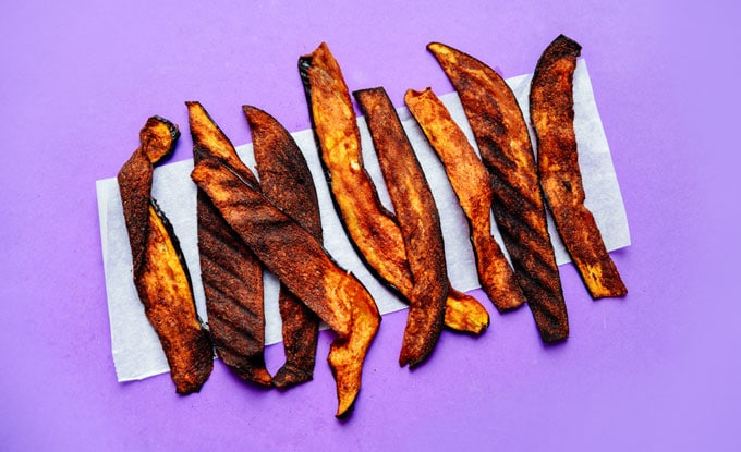 Vegan eggplant bacon recipe on purple background - This vegan Eggplant Bacon recipe takes all the flavor and crispiness of bacon and packs it into thinly sliced bacon!