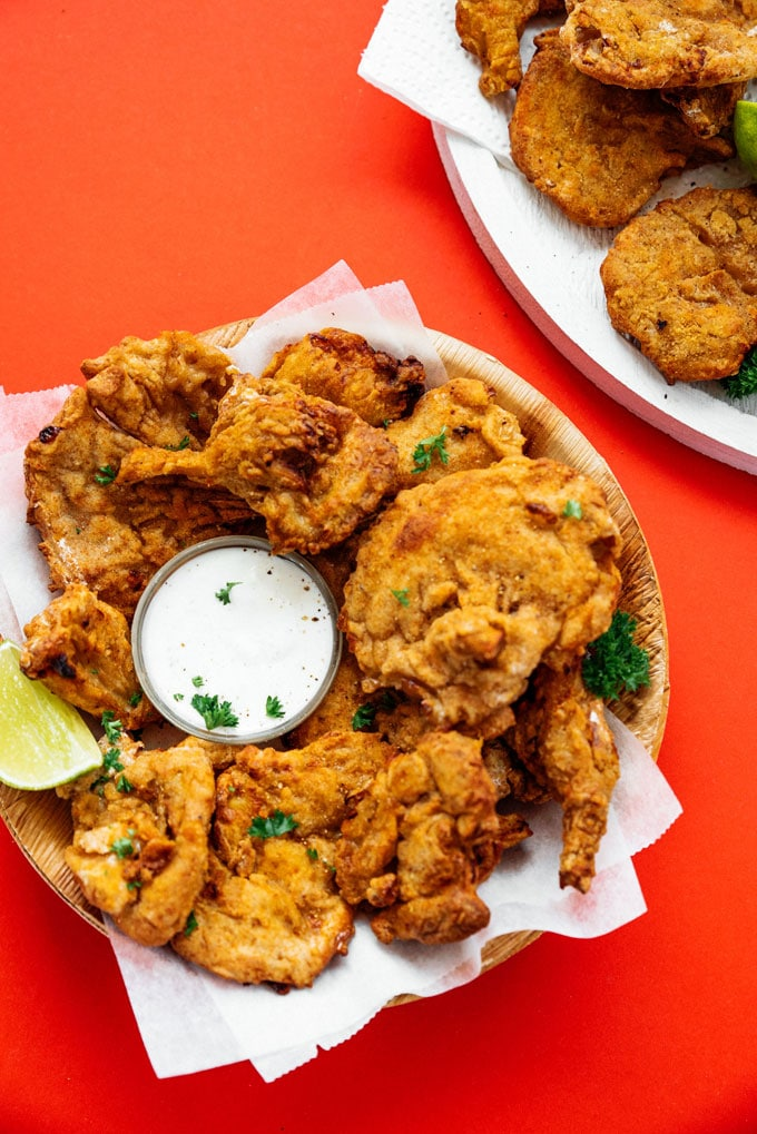 Air fryer fried oyster mushrooms recipe that tastes like vegetarian fried chicken in a bowl on a red background.