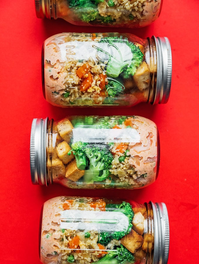 Vegetarian stir fry meal prep recipe idea in mason jars on a red background
