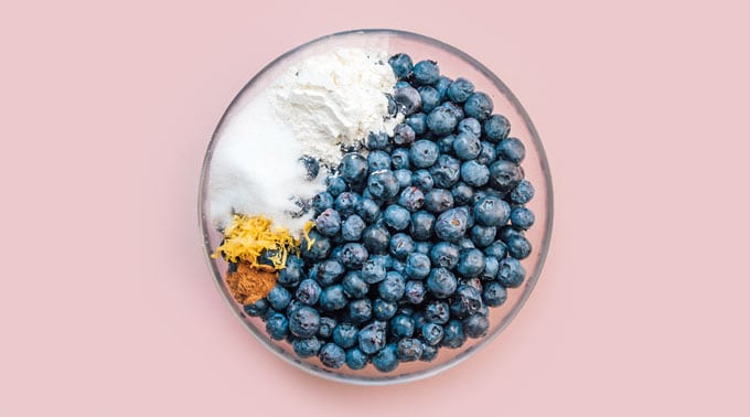Ingredients to make blueberry pie in a a bowl