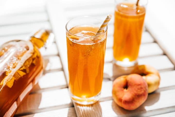 Fizzy peach kombucha in a glass with paper straw