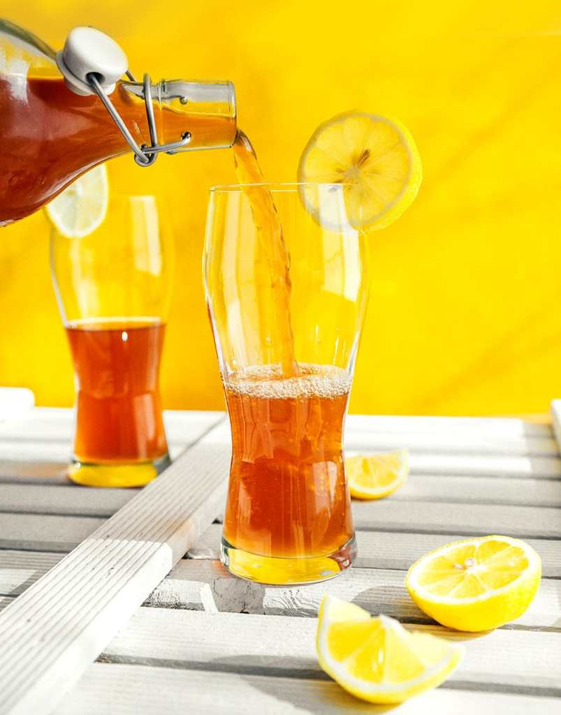 Pouring kombucha into a glass with a yellow background