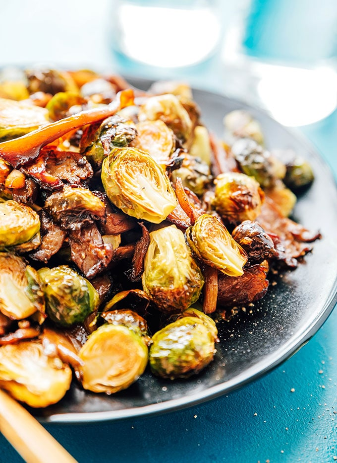 Oven roasted Brussels sprouts with vegan bacon on a black plate