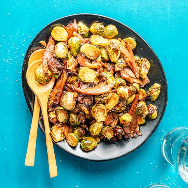Roasted Brussels sprouts with vegan bacon on a black plate