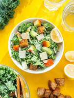 Kale salad with apples and avocado in a bowl on a yellow background