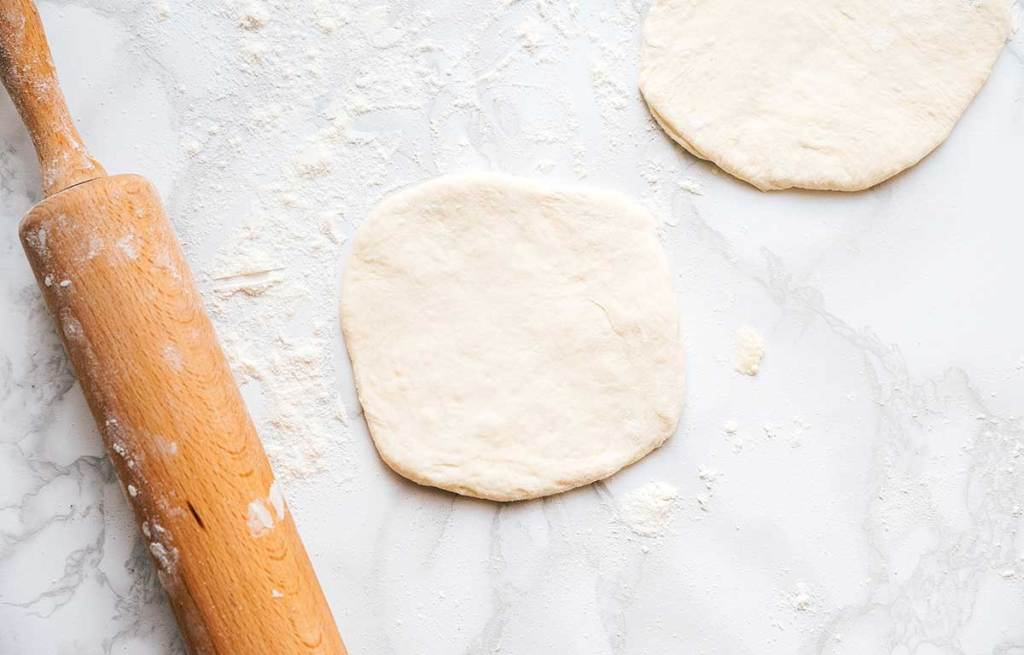 Naan dough slices flattened into flatbreads on a white background