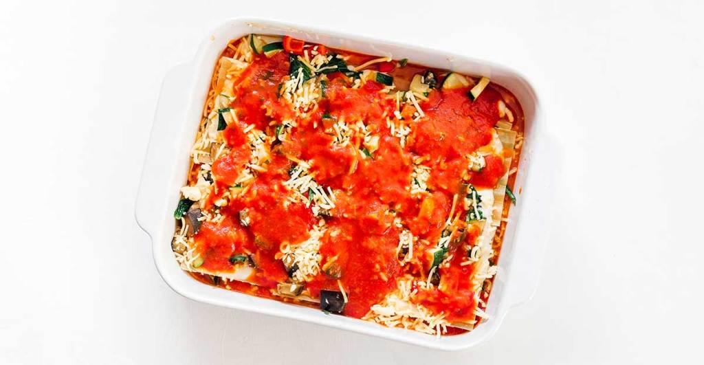 A casserole dish filled with lasagna noodles, bechamel, veggies, mozzarella, and marinara