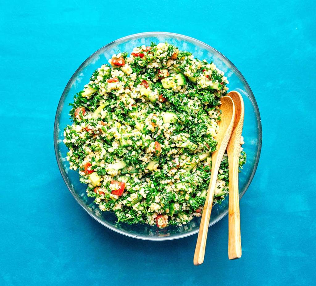 Bird's eye view of a large bowl of tabbouleh salad on a blue background