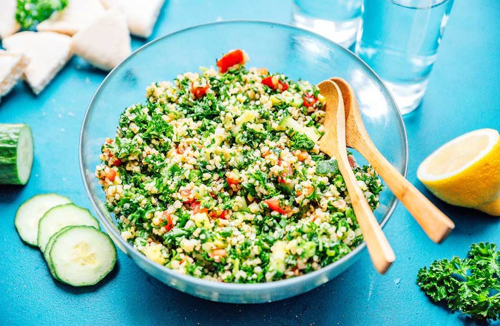 Bird's eye view of a large bowl of tabbouleh salad with various ingredients laid out around the bowl