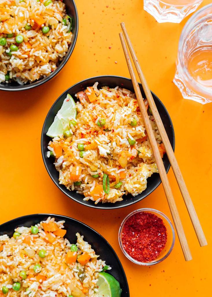 Three bowls of kimchi fried rice on an orange background
