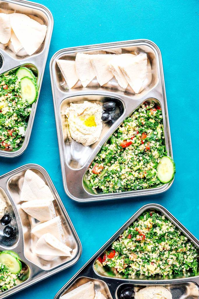 Four meal prep containers on a blue background filled with tabbouleh, hummus, and pita bread