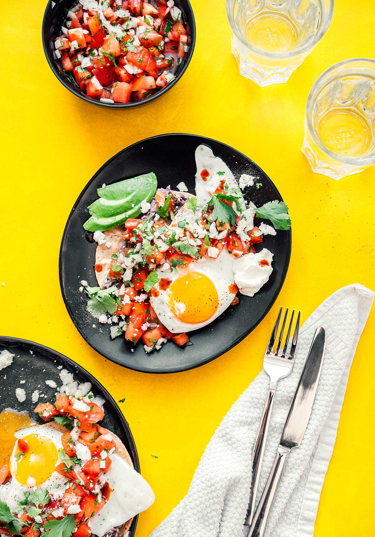 Two plates of huevos rancheros accompanied by two glasses of water and a bowl of pico de gallo
