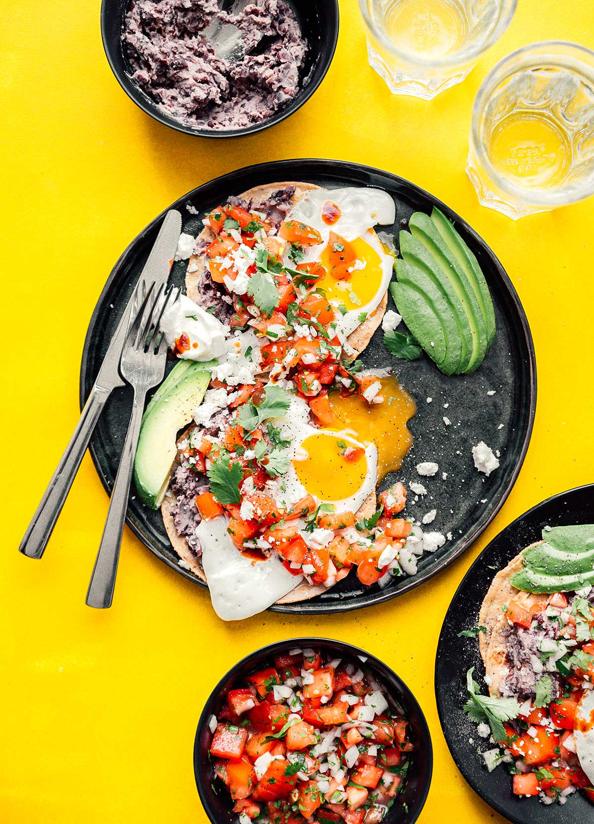Two plates of huevos rancheros accompanied by black beans, water, and pico de gallo