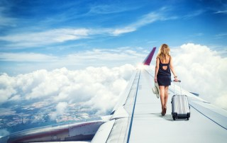 traveler woman walking on an airplane wing carrying a suitcase Travel concept. Anya Andreeva