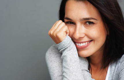 Woman brunette smiling with hands by face