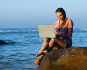 girl working on laptop on a rock at the beach