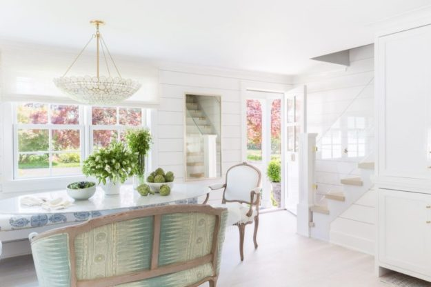A dreamy cape cod style home designed by Raquel Garcia. White interiors, brass and lucite details, open floor plan, and shiplap.