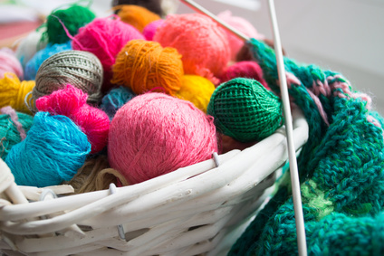 white basket with colored yarns and knitting needles