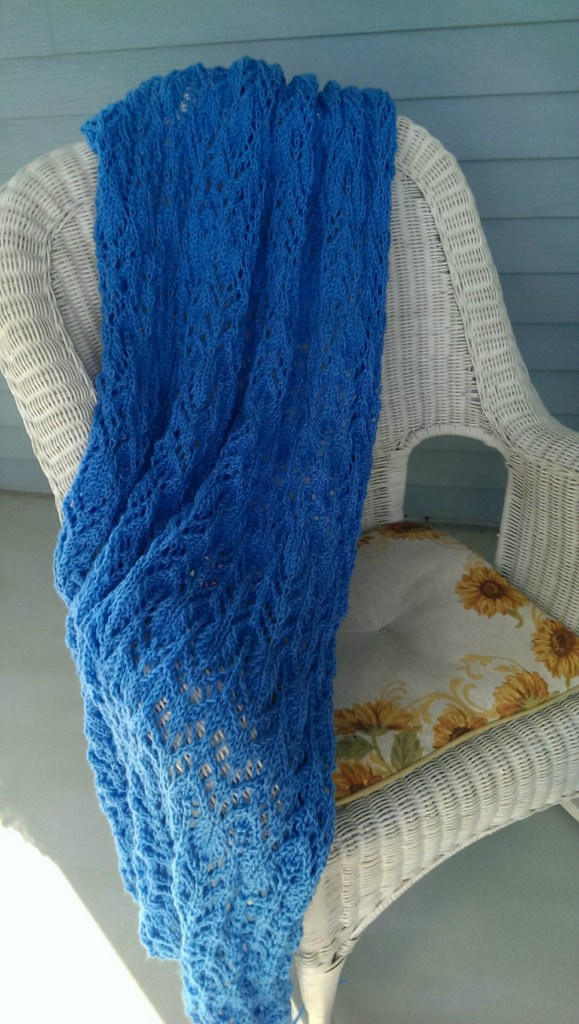 deep blue knit lace afghan on a white wicker chair