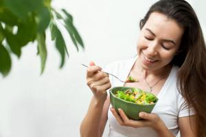 A young woman eating a salad; eating healthy concept, green, plant based diet, nutrition, vegan, eco