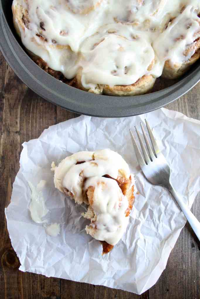 Overhead view of 1 hour cinnamon rolls in a round pan. A half-eaten cinnamon roll and a fork rest nearby on a piece of paper.