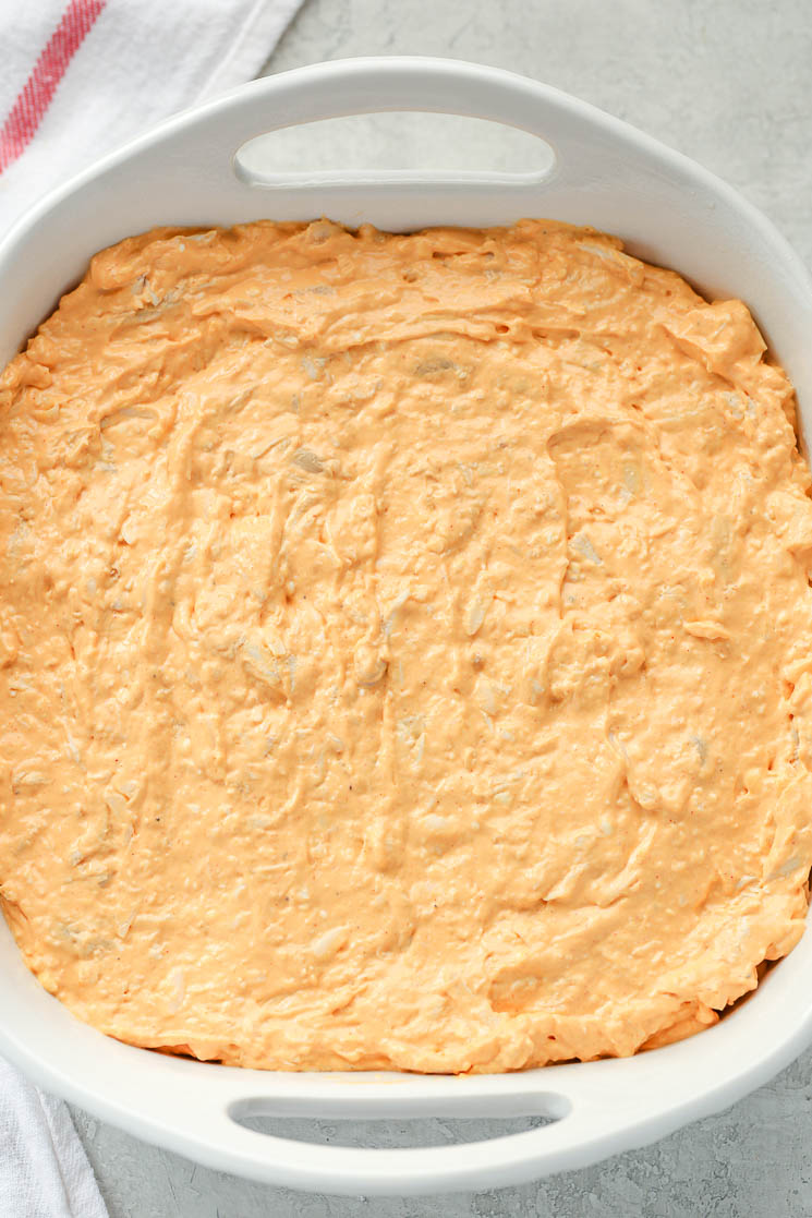 A white 8x8 baking dish filled with creamy buffalo chicken dip and a white napkin on the side.
